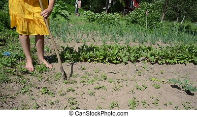 Barefoot woman in yellow dress work grub weeds with hoe in garden.