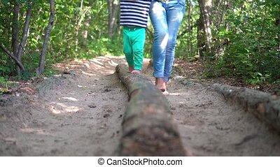 Barefoot woman leading her child boy through tree log on ...