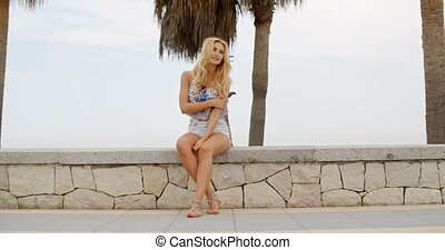 Barefoot Woman Sitting on Stone Wall at Beach - Full Length...