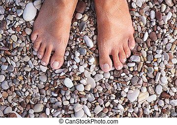 Barefoot woman standing on the pebbles or stones