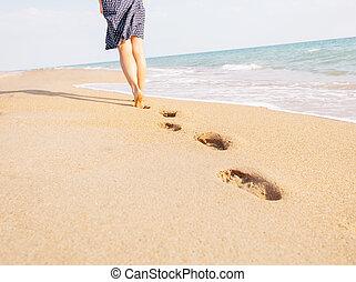 Barefoot woman walking on beach leaving footprints.