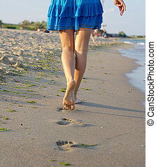 Barefoot woman walking on wet sand - The legs of a barefoot...