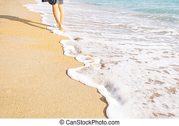 Barefoot young woman walking on sand beach.