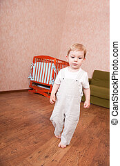 Barefooted boy is walking in his bedroom