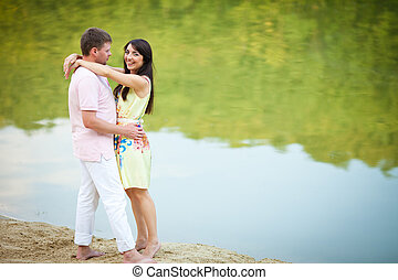 Barefooted couple stands on the lake shore
