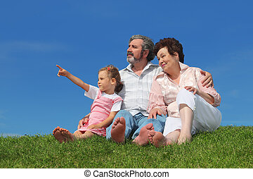 barefooted old man and woman sitting on lawn with their granddaughter, girl pointing by finger at side