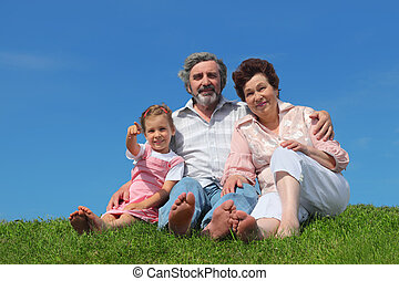 barefooted old man and woman sitting on lawn with their granddaughter, girl pointing by finger