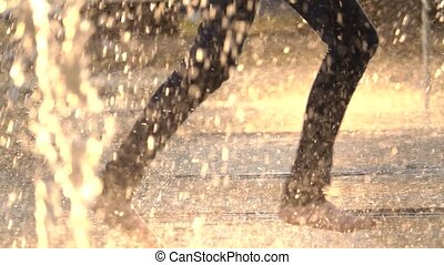 Barefooted person runs between fountain streams, slow motion...