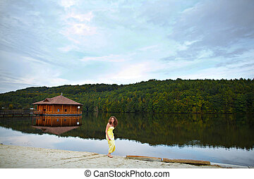 Barefooted woman in yellow dress stands on the lake's shore