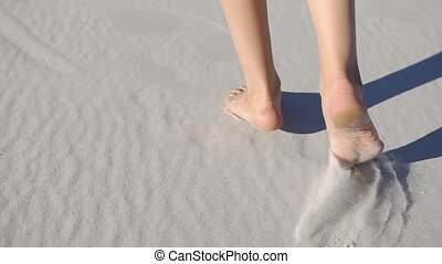 Barefooted woman walks on white sand in a sunny day