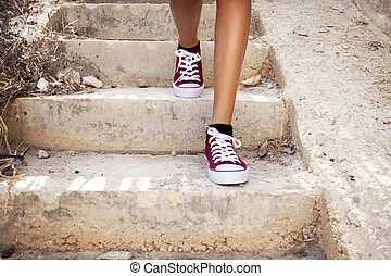 Skinny girls legs with red trainers exercising