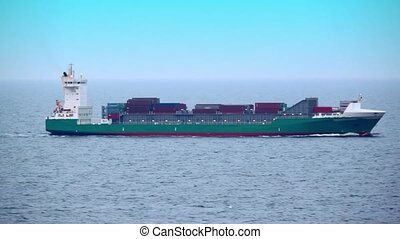 Barge floats in ocean with many containers on deck, shipview...
