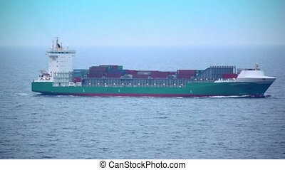 Barge floats in sea with many containers on deck, shipview...