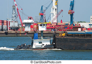 barge in rotterdam harbor with industrial background