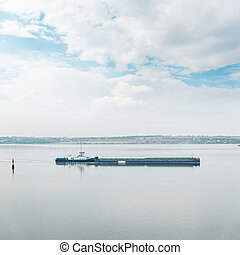 barge on river and clouds in sky