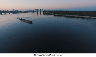 Barge sails along the river near the city port on sunset aerial footage