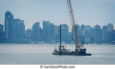 Barge Transporting Crane Near City - Barge carrying large...