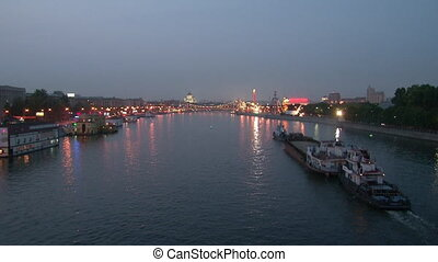Barges are floating along the river in evening.