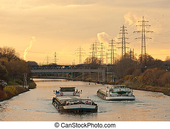 Barges plying waterway channel in industrial area - Inland...
