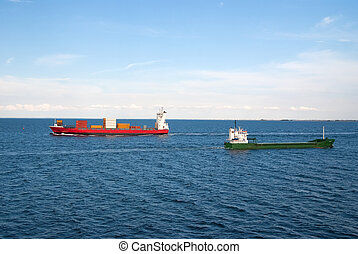 Barges ship cargo containers in sea in Copenhagen, Denmark. Cargo ships float in blue sea on idyllic sky. Marine transport and transportation. Shipping and shipment. Logistics