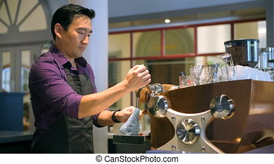 Barista cleaning coffee machine in cafe 4k - Young barista...