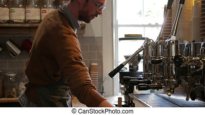 Barista Cleaning the Coffee Machine - Male barista cleaning...