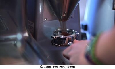 Barista collects freshly ground coffee