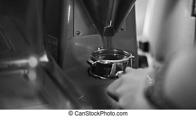Barista collects freshly ground coffee from the grinder(old...
