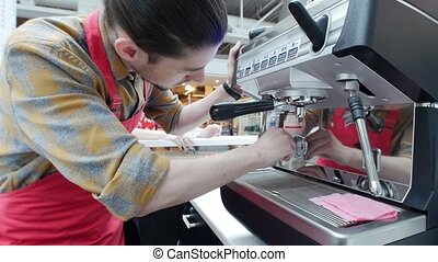 Barista gently wipes a coffee machine in a coffee shop....