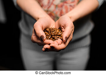 Barista girl holding in her hands little hollow of coffee grains