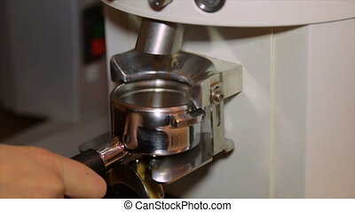 Barista grinding and dispensing ground coffee from grinder...