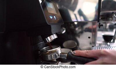 Barista grinding coffee beans using coffee machine - coffee...