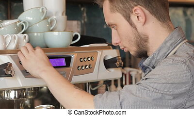 Professional expert barista makes coffee with a coffe machine. Handsome male barista making coffee and smiling while standing at the bar counter near the coffee machine. Barista cafe making coffee preparation service concept.