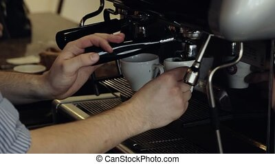 Barista makes espresso in coffee bar. Close-Up.