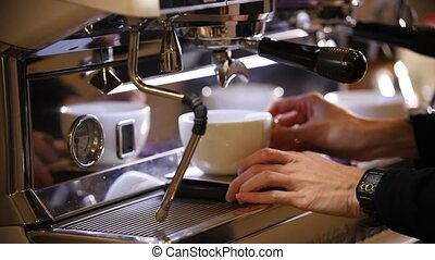 Barista making coffee. An espresso pouring in two cups. Mid...