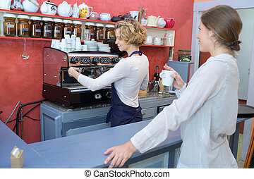 barista making coffee at the bar with female client