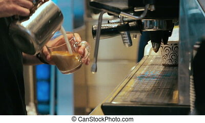Barista making coffee in coffee machine at a busy coffee...