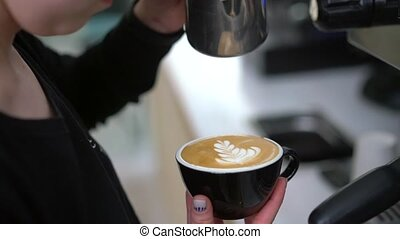 Barista making latte art - Barista pouring steamed milk into...