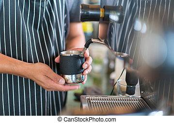 barista making milk for coffee latte or cappuccino