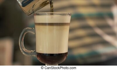 Barista pouring coffee in glass cup with milk for preparing...