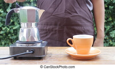 Barista pouring hot coffee from moka pot
