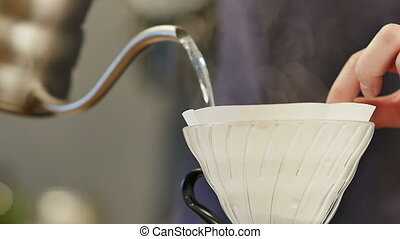 Barista pouring hot water on coffee ground with filter