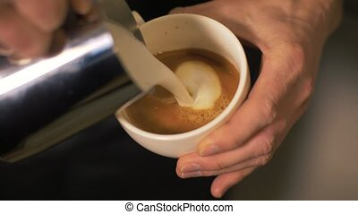 Barista pouring milk in hot coffee and making cappuccino...