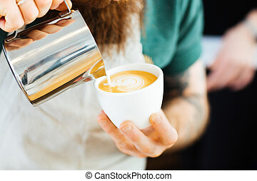 Barista pouring milk into cup of coffee