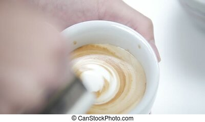 Barista pours a cup of latte coffee and creates a beautiful...