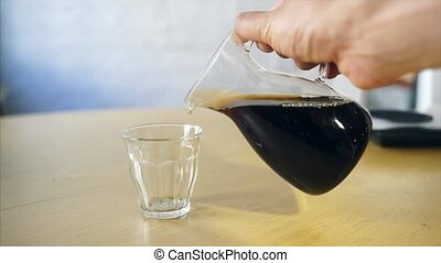Barista pours coffee in a glass mug