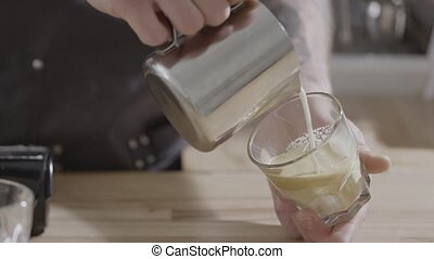 The hands of a man pour milk into a transparent glass of coffee on a wooden table. Cooking latte in a cafe. Full HD video, 240fps, 1080p.