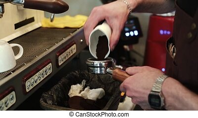 Barista pours freshly ground coffee into the Holder in order to prepare an espresso.