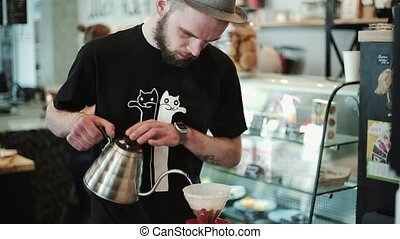 Barista pours hot water into the filter with coffee, stirring. Prepares Pour Over, kemex