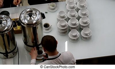 Barista pours tea and coffee during coffee-break at the conference.